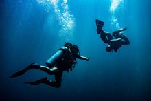 Scuba Diver Reaching Its Diving Partner In Deep Blue Sea