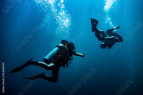 Fototapeta Scuba diver reaching its diving partner in deep blue sea