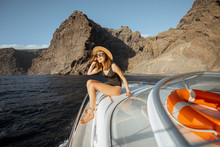 Woman In Swimsuit And Sun Hat Enjoying Ocean Voyage, Sailing On A Yacht Near The Breathtaking Rocky Coast On A Sunset. Concept Of A Luxury Summer Recreational Pursuit And Travel