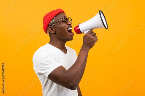 Obraz black african man speaks in megaphone on isolated yellow background - fototapety do salonu