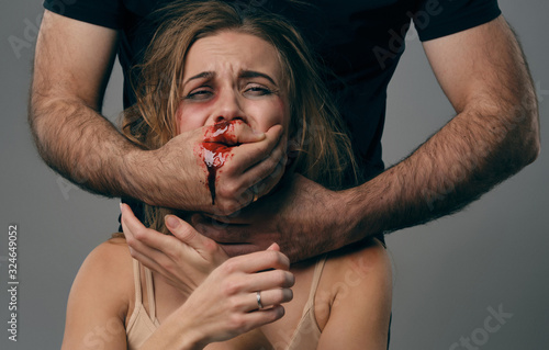 Strong man strangling scared female with bruises on her face Fototapet