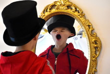 The Child Reflected In A Distorting Mirror. A Fun Reflection Of The Boy. Children's Entertainment