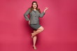 canvas print picture - Charming plus size model girl wearing grey jacket and skirt looking at camera and standing on one leg at pink background, isolated. Young woman in suit. XXL model in official outfit posing over pink.