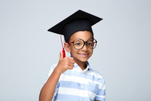 Young African American Boy In Graduation Cap Showing Thumb Up On Grey Background