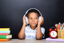 Young African American School Boy Sitting At Desk With Books, Pencils And Headphones On Black Background
