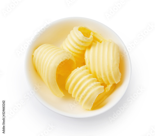 Obraz Butter curls or butter rolls in white bowl isolated. Top view. - fototapety do salonu