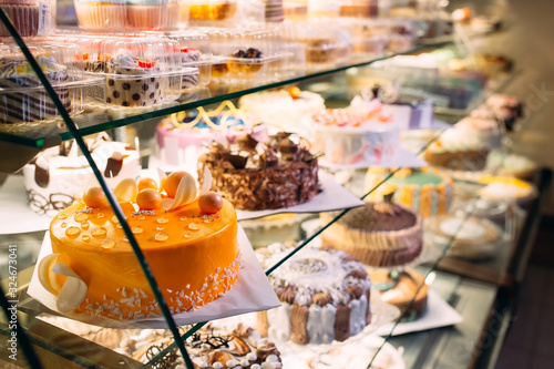 Fototapeta Pastry shop glass display with selection of cream or fruit cake. obraz