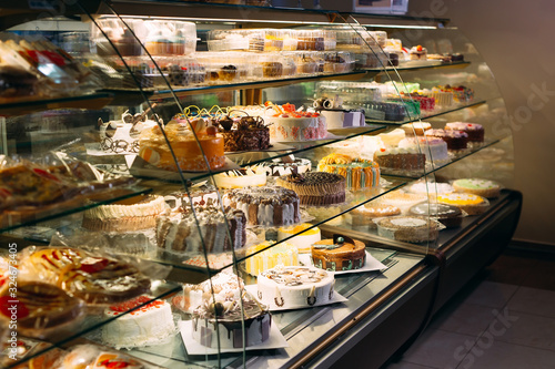Pastry shop glass display with selection of cream or fruit cake. Fototapet