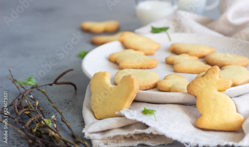 Easter cookies on a ceramic plate with napkin, grey stone background фототапет