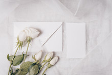 Wedding Invitation Mockup With White Roses , Papers On White Textile Background. Top View, Flat Lay. Wedding Stationary. Perfect For Presentation Of Your Invitation, Menu, Greeting Cards