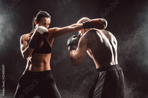 Fotomural Woman exercising with trainer at boxing and self defense lesson, studio, smoke on background
