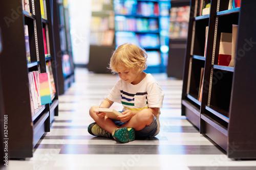 Obraz Child in school library. Kids reading books. - fototapety do salonu