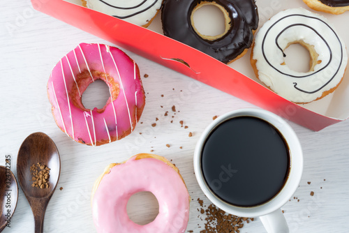 Photo Pinky donut on white table serve with coffee in blur background