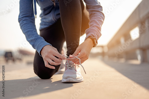 Foto Young women using their hands to tie their shoes jogging in morning workout at the city
