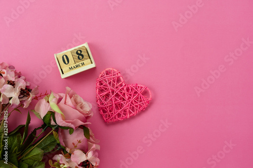 Table top view aerial image of decorations for international women's day  holiday concept background.Flat lay sign of season the word 8 march happy woman's day with flower and gift box on pink paper.