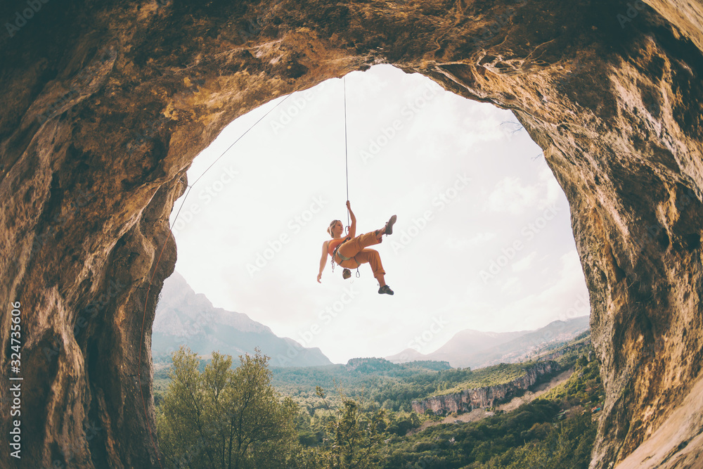 Fototapeta Rock climber hanging on a rope.