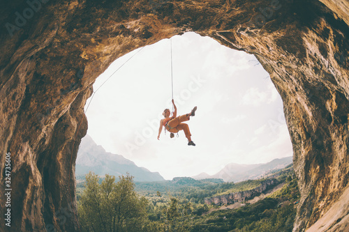 Fotografie, Obraz Rock climber hanging on a rope.