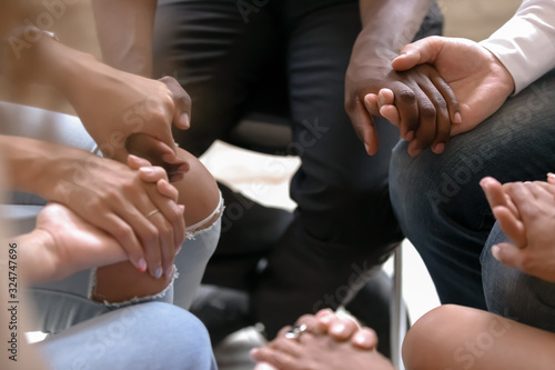 Foto Close up diverse people sitting in circle, holding hands