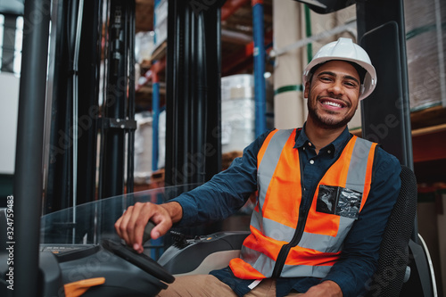 Fotografiet Young forklift driver sitting in vehicle in warehouse smiling looking at camera