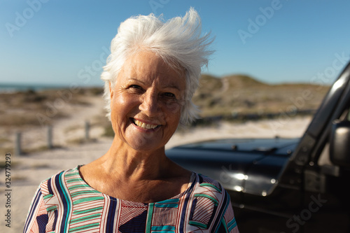 Old woman smiling at the beach