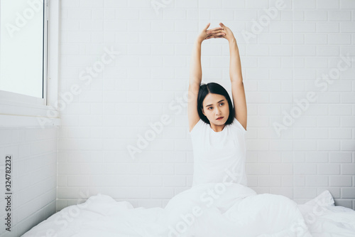 Obraz Beautiful Asian woman waking up on her bed in the bedroom, she is stretching and smiling after wake up, Asia women exercising in the morning, feels refreshed.good dream last night, lifestyle in home - fototapety do salonu