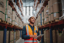 Low Angle View Of Young African Man Wearing Reflective Jacket Holding Digital Tablet Standing In Factory Warehouse Smiling