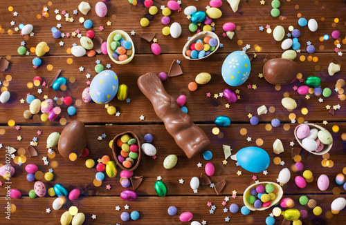 Obraz na plátně easter, sweets and confectionery concept - chocolate eggs, bunny and candy drops
