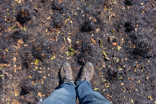 Valokuva Man in blue jeans and trekking boots is standing on the burnt  ground after fire