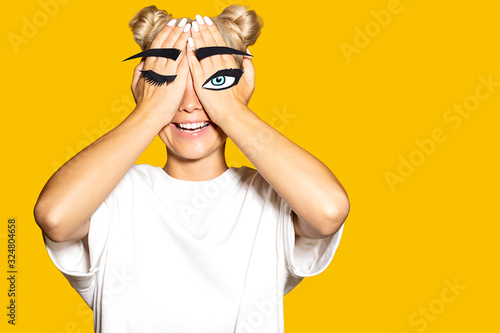 Fotografía Young funny woman covering face with fake giant eyebrows and eyelashes