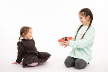 Beautiful Teen Girl In Blue Hoodie Shows Present Box To Her Little Redhead Sister In Dress, Isolated Over White Background