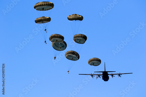 Fototapeta Military parachutist paratroopers jumping out of an air force airplane