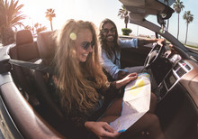 Happy Young Couple Reading City Map Inside Convertible Sport Car - Travel People Having Fun On Hoildays Doing Road Trip - Vacation, Journey And Relationship Concept - Main Focus On Girl Face