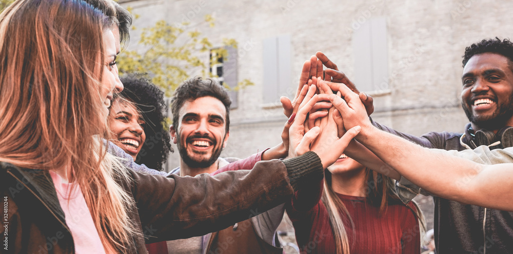 Fototapeta Young happy people stacking hands outdoor - Diverse culture students celebrating together - Youth lifestyle, university, relationship, human resorces, work and friendship concept - Focus on hands
