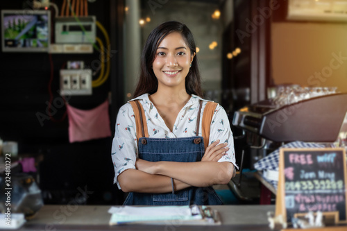 Asian women Barista smiling and using coffee machine in coffee shop counter - Wo Canvas Print