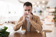 young bearded attractive man sneezing while drinks coffee during his lunch break in the cafe, healthcare and medicine context