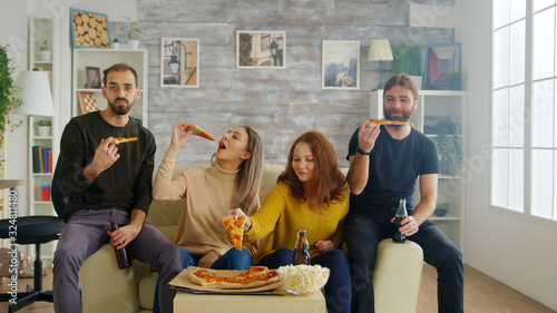 Group of friends laughing hard while a sitcom on tv Canvas Print