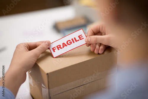 Obraz delivery, mail service, people and shipment concept - close up of woman sticking fragile mark to parcel box at post office - fototapety do salonu