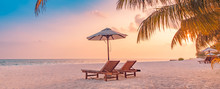 Best Beach Sunset Panorama. Tropical Landscape Scene. Amazing Sunset Sea View With Palm Leaves And Two Lounge Chairs With Umbrella. Luxury Lifestyle, Travel And Summer Vacation Background