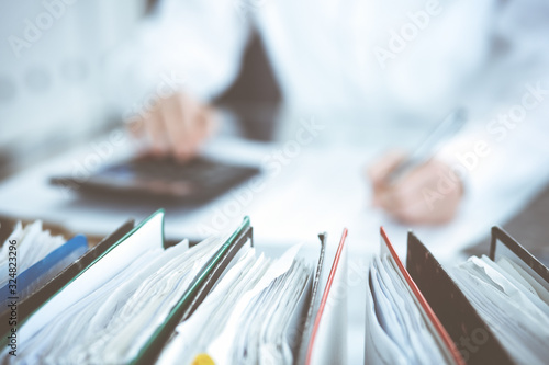 Fototapeta Binders of papers waiting to process by bookkeeper woman or financial inspector, close-up. Business portrait. Audit or tax concepts obraz