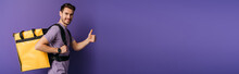 Panoramic Shot Of Happy Delivery Man Showing Thumb Up While Looking At Camera On Purple Background