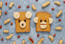 Funny Bear And Monkey Face Sandwich With Peanut Butter, Banana And Black Currant,peanuts On Grey Concrete Background,top View