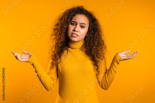 Young curly unsure girl shrugs her arms, makes gesture of I don't know, care, can't help anything Wallpaper Mural
