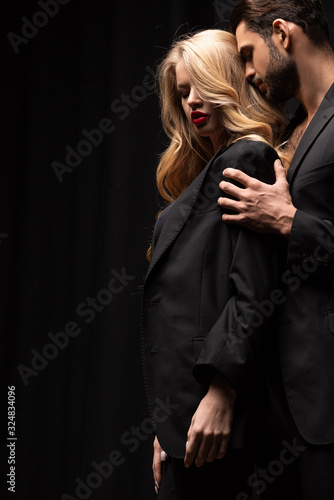 Fototapeta handsome man touching beautiful woman in suit isolated on black obraz