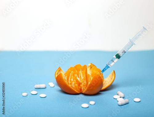 Obraz na plátne Medicine concept with fresh injured mandarin and tablets