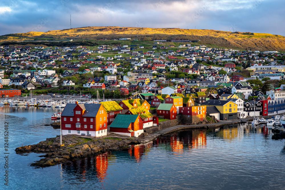 Fototapeta Sunrise scene of capital city Torshavn in Faroe Islands in North Atlantic. Urban scene of scandinavian city in warm golden sunlight.