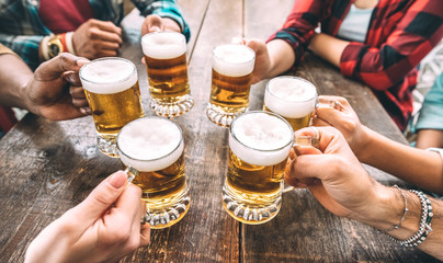 Friends hands toasting beer pints at brewery pub restaurant - Beverage concep...