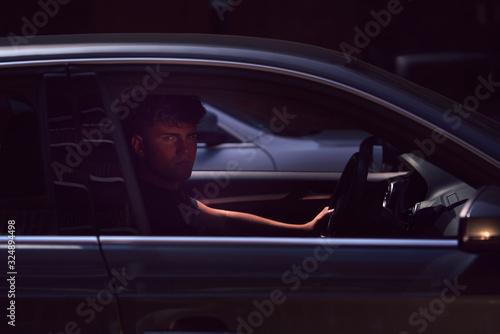 Photo Ein junger gutaussehender Mann sitzt im Auto und schaut verführerisch in die Kamera