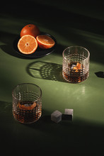 Old Fashioned Cocktail In Retro Glasses With Oranges And Whiskey Stones On Green Table Top