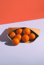 Oranges In A Container On Red And Blue Background