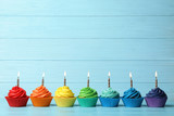 Fototapeta Tęcza - Delicious birthday cupcakes with burning candles on blue wooden table